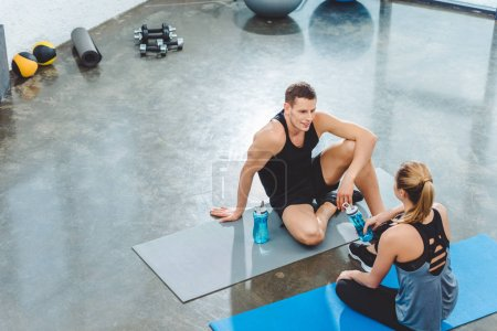 Photo for High angle view of sportsman and sportswoman with bottles of water sitting on yoga mats and looking at each other in gym - Royalty Free Image