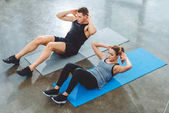 high angle view of sporty young couple doing abs exercise in gym