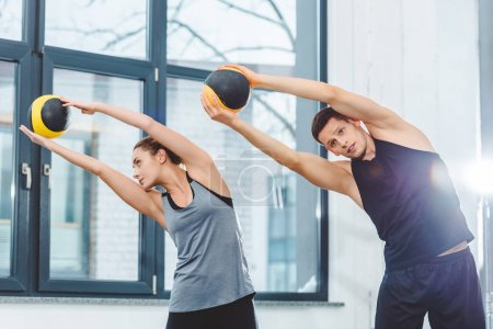 sporty young couple holding balls and training together in gym