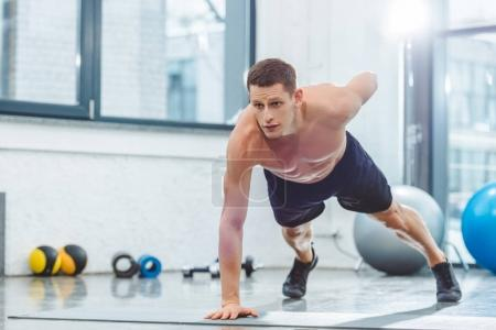 handsome shirtless young sportsman doing push ups on yoga mat