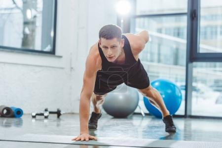 handsome young sportsman doing push ups on yoga mat