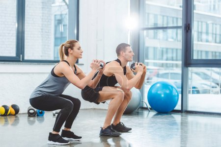 Photo for Sporty young couple holding dumbbells and doing squat exercise in gym - Royalty Free Image