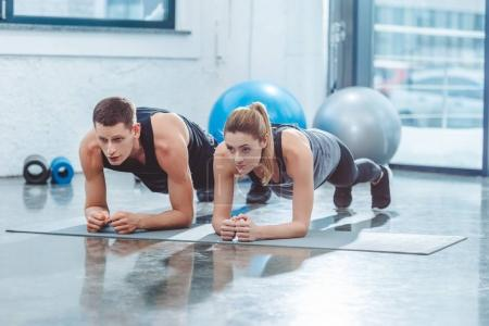Photo for Sporty young couple doing plank exercise in gym - Royalty Free Image