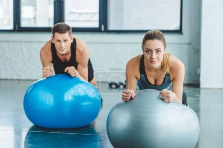 young man and woman exercising on fitness balls in gym