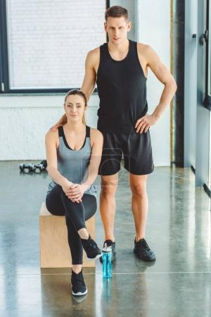 young sportive couple looking at camera in gym
