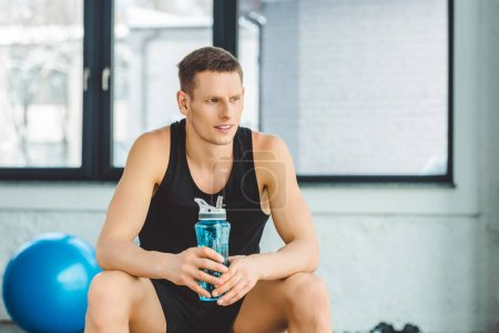 portrait of sportsman with water bottle resting after training in gym