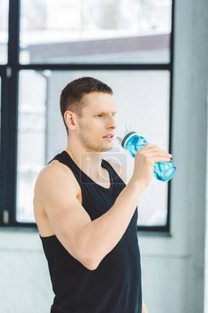 Photo for Portrait of sportsman drinking water from sportive bottle after training in gym - Royalty Free Image