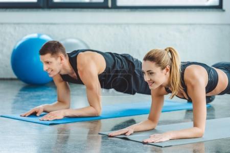 Photo pour Couple faisant des exercices abdominaux sur les tapis avant l'entraînement dans la salle de gym - image libre de droit