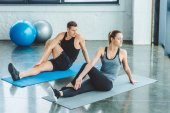 couple stretching on mats before workout in gym