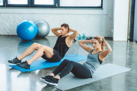 Photo for Couple doing abs exercises on mats before workout in gym - Royalty Free Image