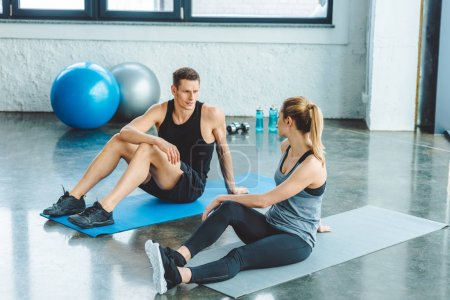 couple resting on mats after workout in gym