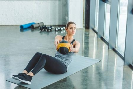 focused sportswoman doing exercises with ball in gym