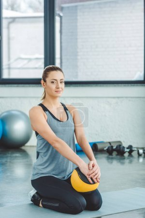 smiling sportswoman with ball resting on mat in gym