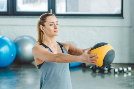 portrait of sportswoman doing exercises with ball in gym