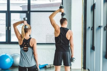 back view of couple in sportswear training with dumbbells in gym