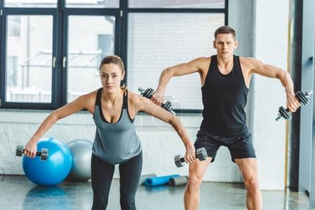focused couple in sportswear training with dumbbells in gym
