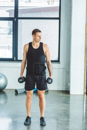 Photo for Young sportsman working out with dumbbells in gym - Royalty Free Image