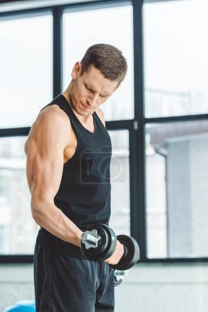 side view of young sportsman working out with dumbbells in gym