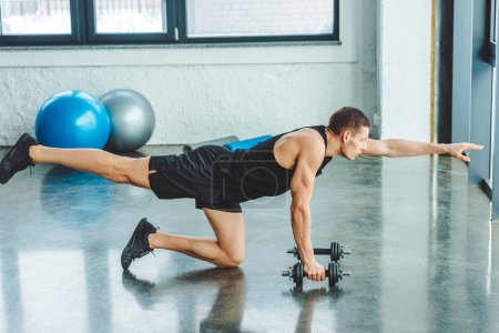 Photo for Side view of young sportsman working out with dumbbells in gym - Royalty Free Image
