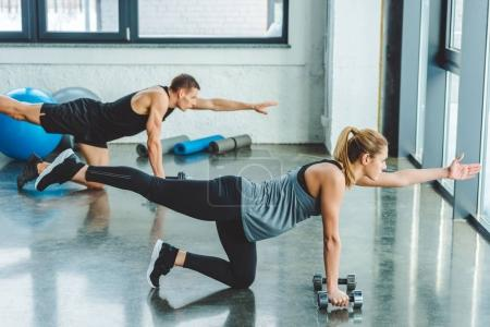 couple in sportswear training with dumbbells in gym