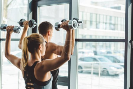 back view of young man and woman looking out window while exercising with dumbbells in gym