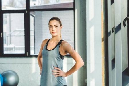 Photo pour Portrait de jeune femme caucasienne sur les hanches en vêtements de sport en salle de gym - image libre de droit