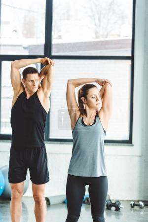 portrait of young couple warming up before workout in gym
