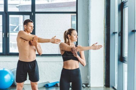 young couple stretching before workout in gym
