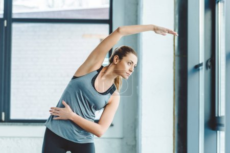 portrait of young sportswoman warming up before workout in gym