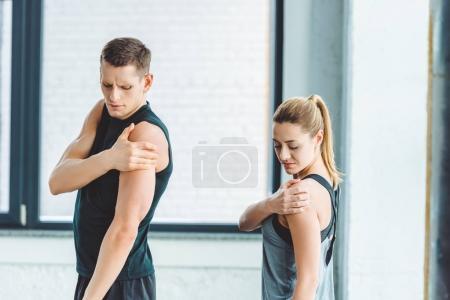 Photo pour Jeune couple étirement avant l'entraînement en gymnase - image libre de droit