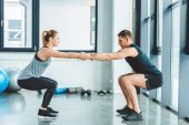 side view of caucasian man and woman training in gym together