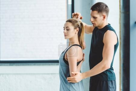side view of trainer helping woman to warm up before workout