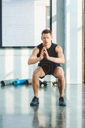 concentrated young sportsman working out in gym