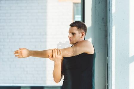 side view of young man stretching before workout in gym