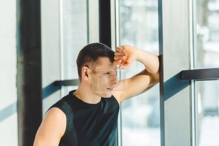 side view of pensive sportsman looking out window in gym