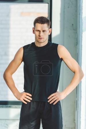 portrait of young sportsman akimbo in sportswear standing in gym