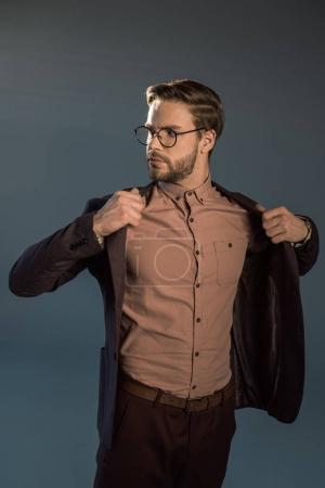 Photo for Portrait of stylish man in eyeglasses wearing jacket and looking away isolated on grey - Royalty Free Image
