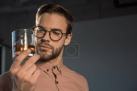 close-up view of stylish young man in spectacles holding glass of whisky