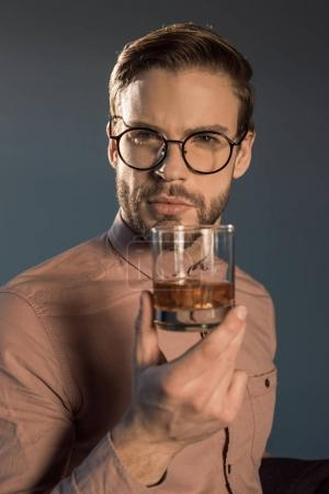 close-up view of stylish young man in spectacles holding glass of whisky and looking at camera isolated on grey