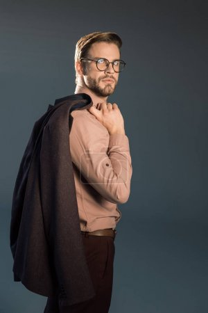 Photo for Portrait of handsome stylish young man in spectacles holding suit jacket and posing isolated on grey - Royalty Free Image