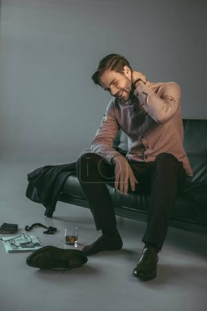 young businessman suffering from pain in neck while sitting on couch