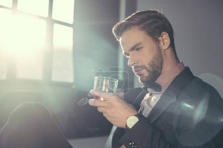 handsome bearded young man holding eyeglasses and glass of whisky