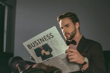 handsome stylish young man reading business newspaper