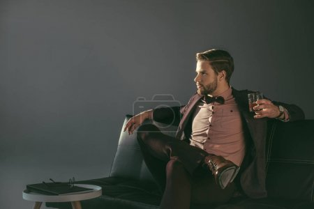 Photo for Young businessman holding glass of whiskey and looking away isolated on grey - Royalty Free Image