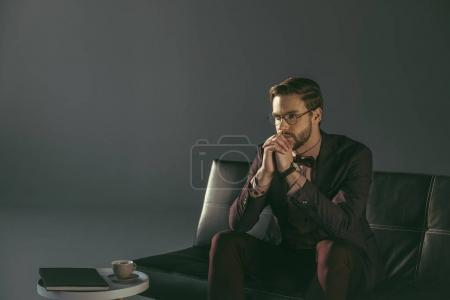 Photo for Pensive young stylish man in eyeglasses sitting on couch and looking away - Royalty Free Image