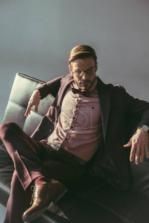 stylish young businessman in eyeglasses sitting on couch and looking away on grey