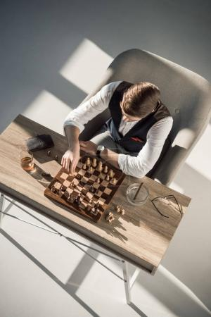 overhead view of businessman playing chess while drinking whisky and smoking cigar