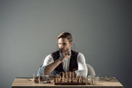 Photo for Stylish young businessman with cigar looking away while playing chess - Royalty Free Image
