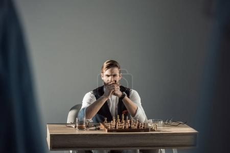selective focus of stylish businessman with cigar looking at camera while playing chess