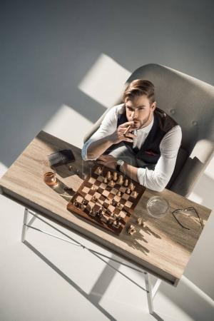 overhead view of young businessman with cigar looking at camera while playing chess